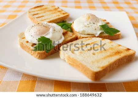 Poached eggs on white plate - stock photo