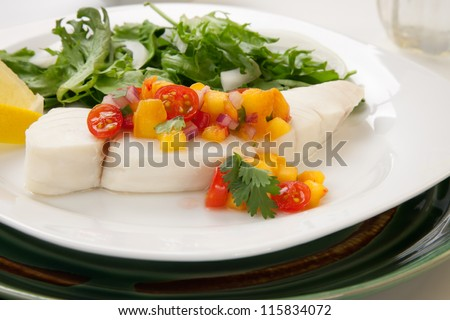 Poached halibut with peach salsa, and green salad. - stock photo