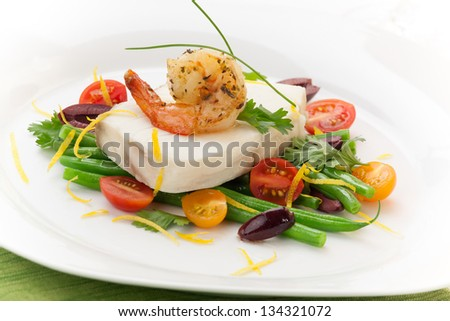 Poached halibut with spicy shrimp, green beans, cherry tomatoes, black olives, and citrus sauce. - stock photo