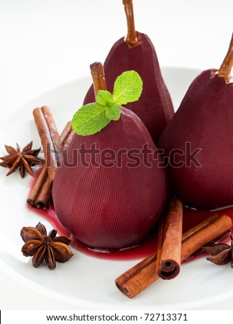 Poached pears in red wine with spices. Shallow dof. - stock photo
