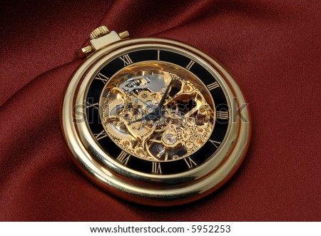 Pocket clock in gold showing the mechanism on red fabric - stock photo