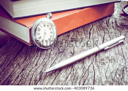 Pocket watch and book with pen, On old textured wood. Vintage style. - stock photo
