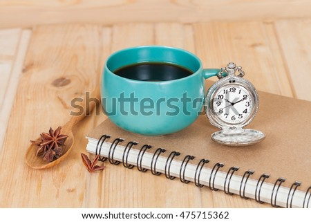 pocket watch and coffee cup on book