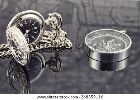 pocket watch and compass lying on the reflecting surface