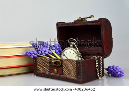 Pocket watch, flowers, books and treasure chest - stock photo