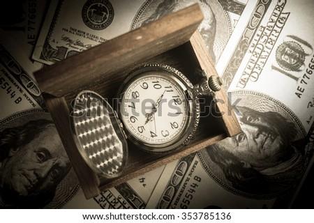 Pocket watch in wood box on money. - stock photo