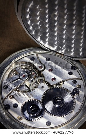Pocket watch inside on wooden desk with wheels and springs silver color