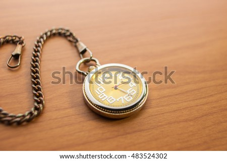 Pocket watch on wooden, close up, some blurred area.