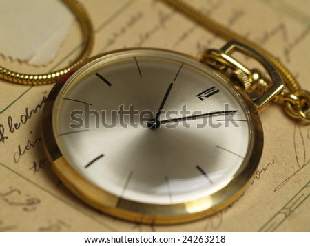 pocket watch over old postcards