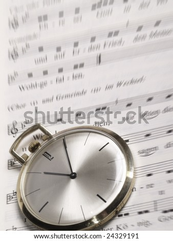 pocket watch over old sheet of music