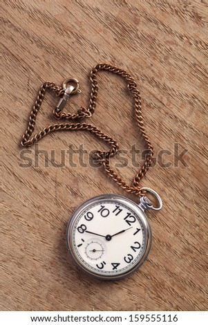 Pocket watch with chain on a wooden table