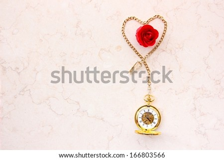 Pocket watch with heart shape chain and red rose on marble. - stock photo