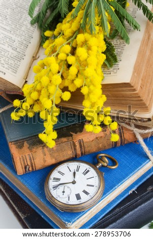 pocket watch with stack of vintage old books - stock photo