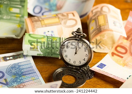 pocket watch with various banknotes in the background  - stock photo