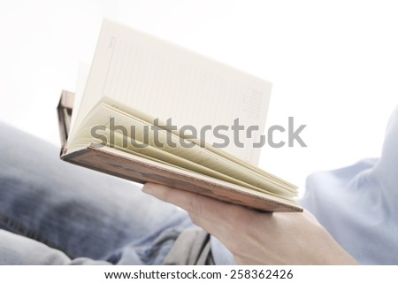pocketbook in woman hand - stock photo