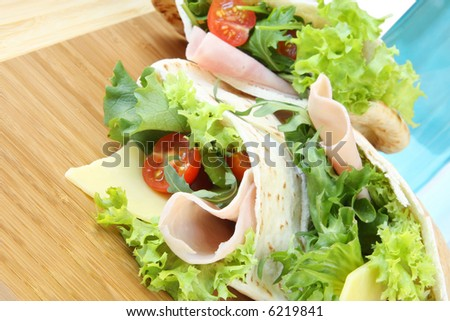 Pockets of pitta bread, filled with ham and salad. - stock photo