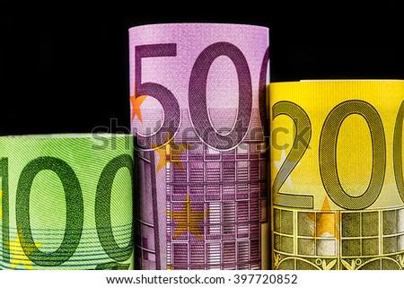 podium made of three big euro banknotes on black background - stock photo
