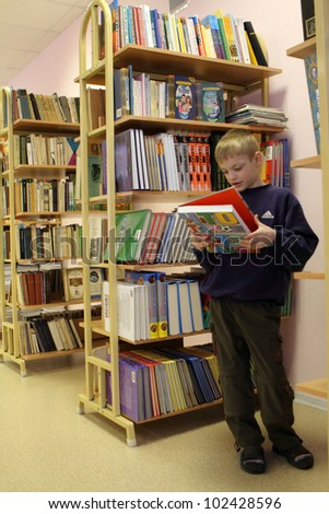 PODPOROZHYE, RUSSIA - JANUARY 31: Open Day at the Podporozhye's Children House - unknown kid in the library read books, January 31, 2010 in Podporozhye, Russia. - stock photo