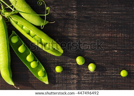Pods of green peas and pea on a dark wooden surface, top view - stock photo