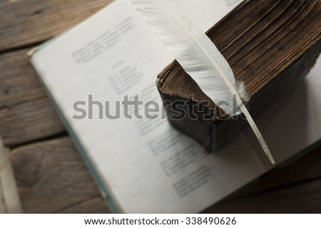 Poet, writer, literature idea. Old book, book of poems and a feather. - stock photo