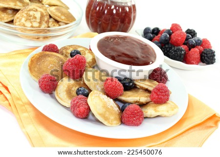 Poffertjes baked with raspberries and blueberries - stock photo