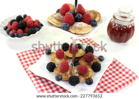 Poffertjes with berries on a cake stand on a light background