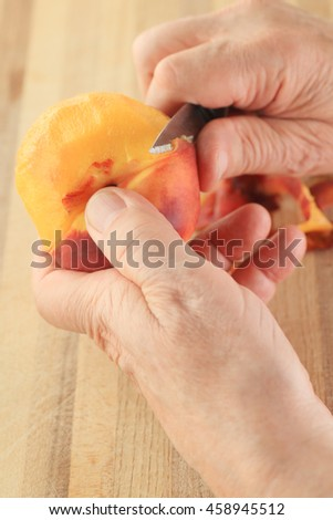 Point of view of man peeling a fresh peach - stock photo