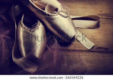 Pointe shoes on wooden background - stock photo