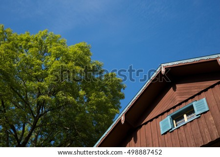 Pointed roof of a residential house next to a tree