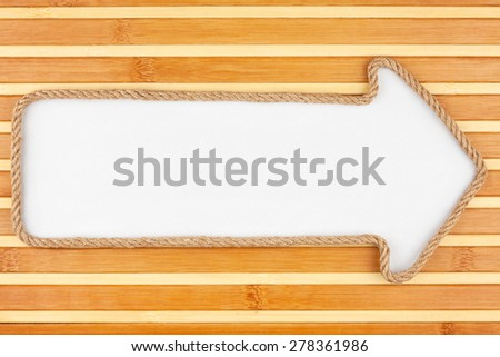Pointer made of rope with a white background on the bamboo mat, with place for your text - stock photo