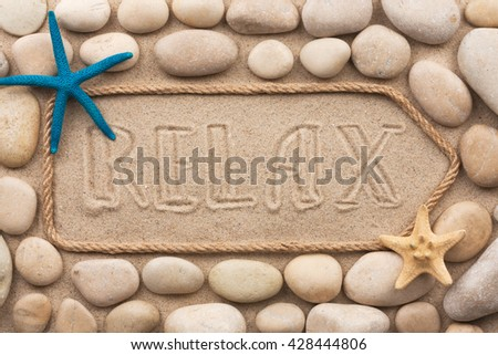 Pointer made of rope with an inscription RELAX with white stone, on sand - stock photo