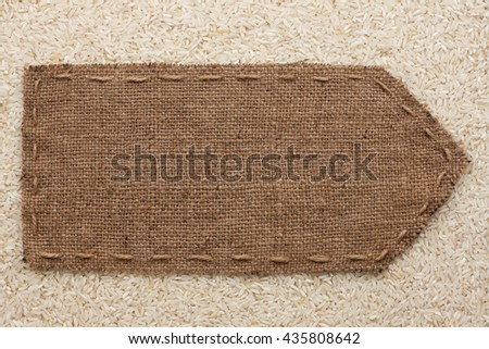 Pointer of burlap lying on a rice background, with place for your text - stock photo