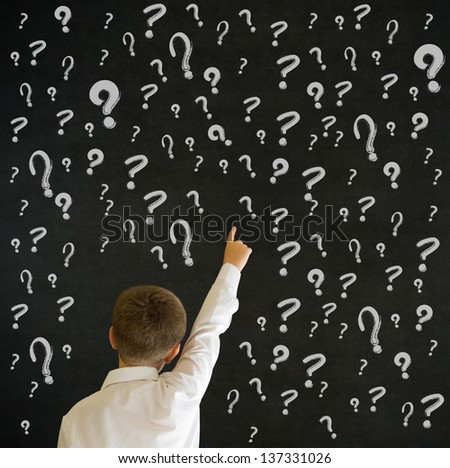 Pointing boy dressed up as business man with chalk questions marks on blackboard background - stock photo