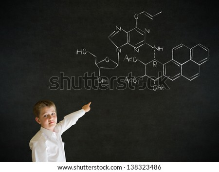 Pointing boy dressed up as business man with science or chemistry formula on blackboard background - stock photo
