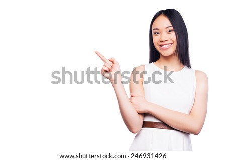 Pointing copy space. Beautiful young Asian woman pointing away and smiling while standing against white background - stock photo