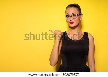 Pointing copy space. Bright studio portrait of attractive young woman pointing copyspace with her thumb. - stock photo