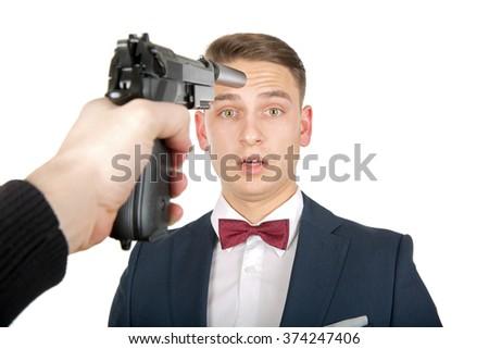Pointing handgun on a business man's head - stock photo