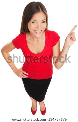 Pointing showing woman smiling cheerful. Funny high angle portrait of a beautiful happy woman pointing with her finger at copy space. Multiracial Asian Caucasian business woman isolated on white. - stock photo