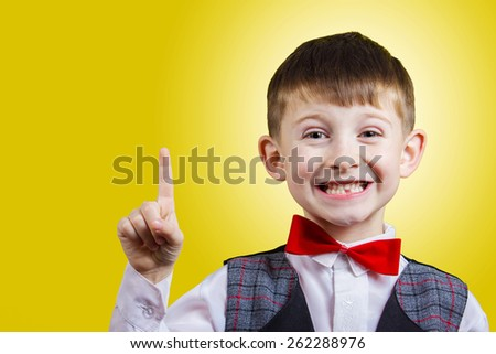 Pointing up  smiling little boy isolated over yellow background. - stock photo