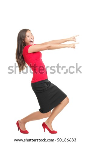 Pointing woman. Happy excited woman pointing sideways while standing in full length profile. Isolated on white background. - stock photo
