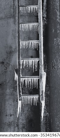 Pointy icicles hang down from rusty iron ladder. Black an white tinted in blue - stock photo