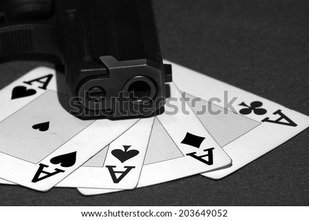 Poker aces with a cannon gun in black and white - stock photo