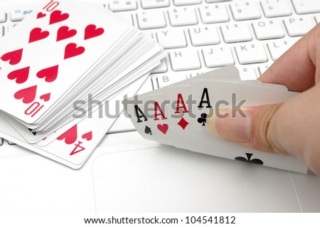 Poker and the computer keyboard (the expression of an online poker game or against the concept of online gambling) - stock photo