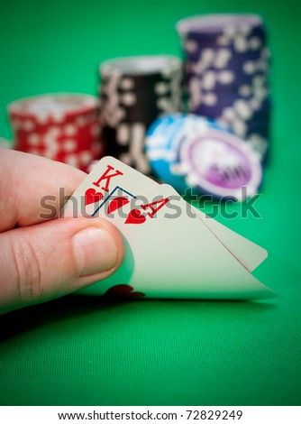Poker chips and a hand flip the cards  against green felt - stock photo