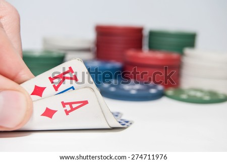 Poker chips and a hand hold the cards isolated - stock photo