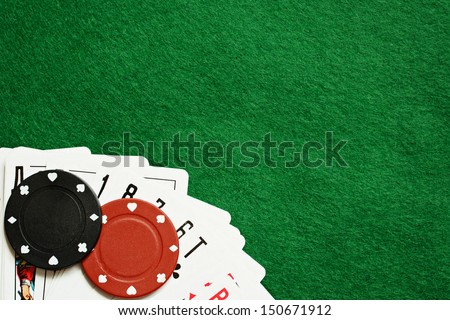Poker chips and cards on green cloth - stock photo