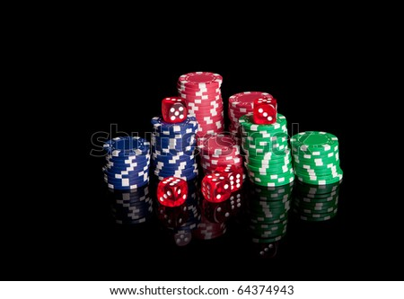 Poker chips and dices, isolated over black background - stock photo