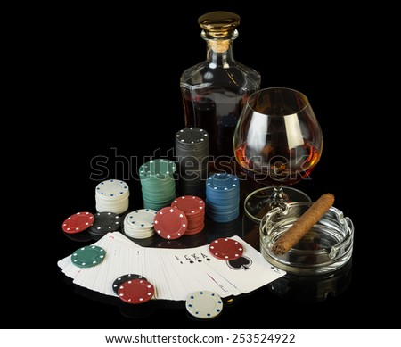 Poker chips and playing cards on black background - stock photo