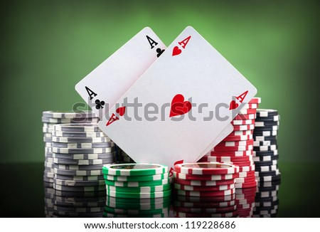 Poker chips and playing cards on green background - stock photo