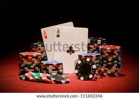Poker chips and playing cards on red background